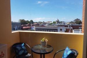 The Balcony and Cafe Bistro Setting of Hamilton 1 Bedroom Studio.